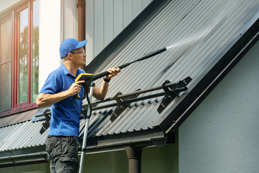 Man Standing On Ladder And Cleaning House Metal Roof - Vancouver